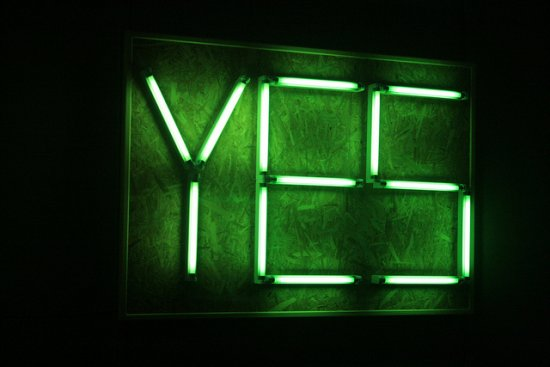 Neon green yes sign on black background
