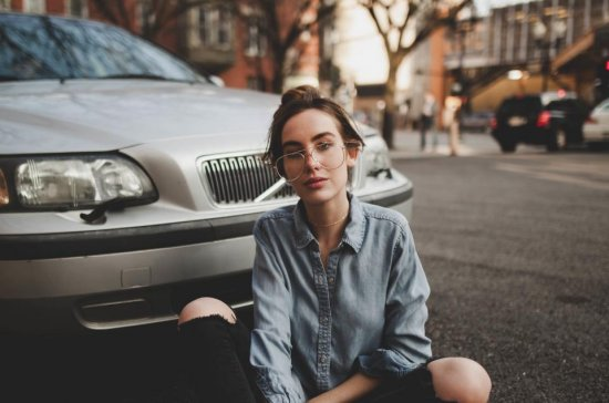 Woman sitting in front of leased car